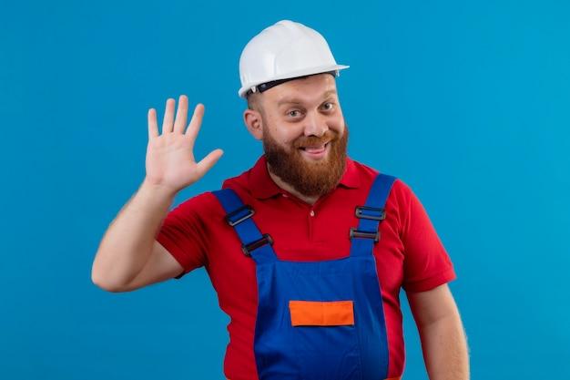 Jonge, bebaarde bouwersmens in bouwuniform en veiligheidshelm die vrolijk met hand glimlachen zwaaien