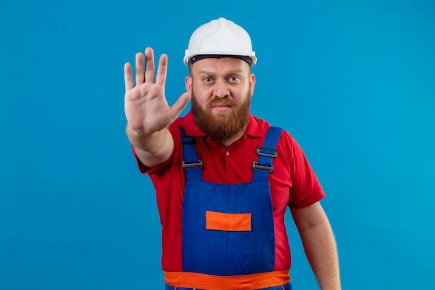 Jonge, bebaarde bouwersmens in bouwuniform en veiligheidshelm die zich met open hand bevinden die stopbord maken die ontevreden over blauwe achtergrond kijken
