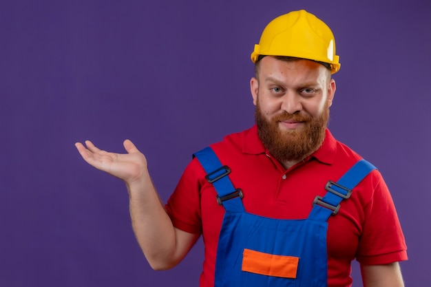 Jonge, bebaarde bouwersmens in bouwuniform en veiligheidshelm glimlachend presenteren met arm van zijn hand kopiëren ruimte op paarse achtergrond
