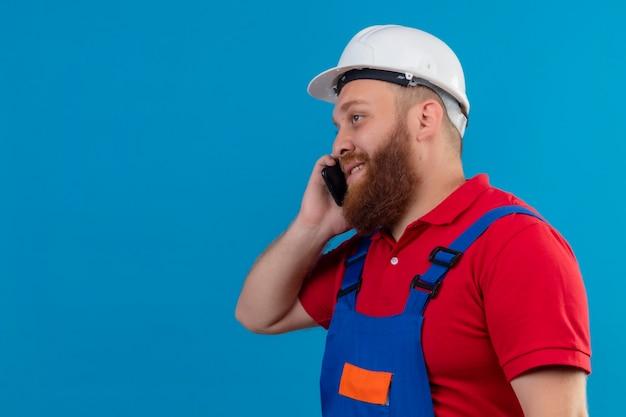 Jonge, bebaarde bouwersmens in bouwuniform en veiligheidshelm glimlachend sprekend op mobiele telefoon