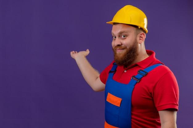 Jonge, bebaarde bouwersmens in bouwuniform en veiligheidshelm glimlachend zelfverzekerd presenteren iets achter hem met arm van zijn hand over paarse achtergrond