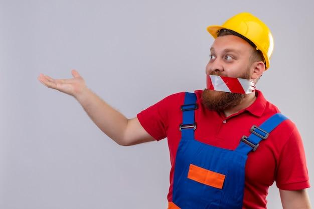 Jonge, bebaarde bouwersmens in bouwuniform en veiligheidshelm met band over zijn mond die opzij verrast met opgeheven hand kijken