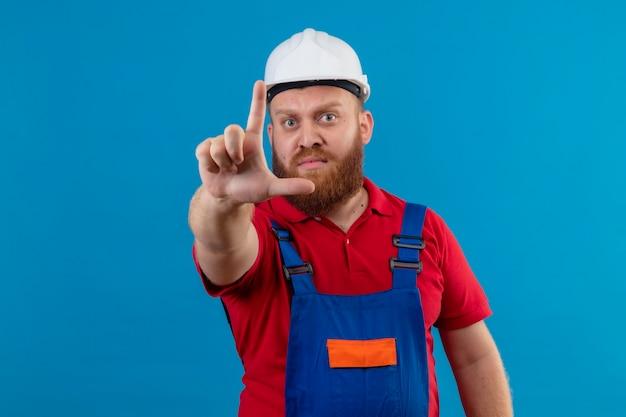 Jonge, bebaarde bouwersmens in bouwuniform en veiligheidshelm met ernstig gezicht wijzende wijsvinger, waarschuwingsgebaar
