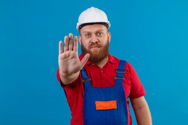 Jonge, bebaarde bouwersmens in bouwuniform en veiligheidshelm met open hand die stopbord met ernstig gezicht maken