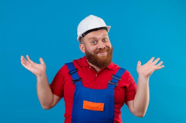 Jonge, bebaarde bouwersmens in bouwuniform en veiligheidshelm met opgeheven handpalmen, schouders ophalend glimlachen, zonder antwoord