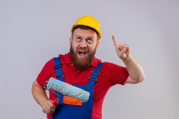 Jonge, bebaarde bouwersmens in bouwuniform en veiligheidshelm met verfroller wijzende wijsvinger omhoog schreeuwen