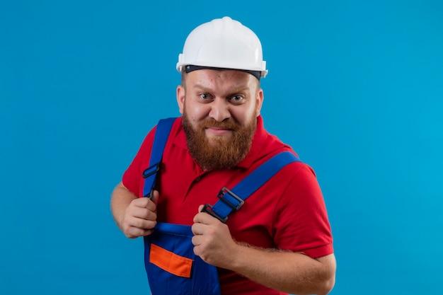 Jonge, bebaarde bouwersmens in bouwuniform en veiligheidshelm ontevreden met boos gezicht