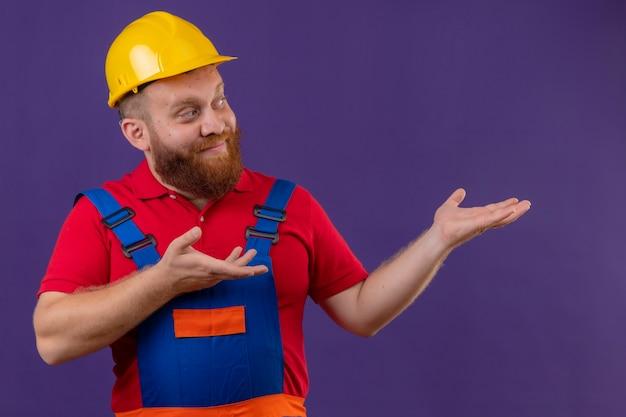 Jonge, bebaarde bouwersmens in bouwuniform en veiligheidshelm op zoek opzij presenteren met armen oh zijn handen op paarse achtergrond