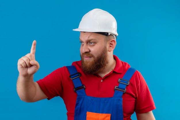 Jonge, bebaarde bouwersmens in bouwuniform en veiligheidshelm op zoek opzij verward wijzende vinger omhoog
