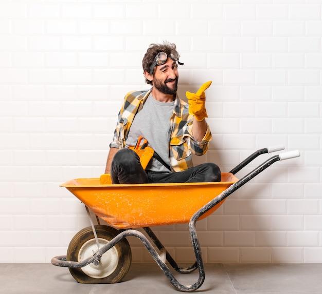 Jonge, bebaarde bouwvakker man op een kruiwagen