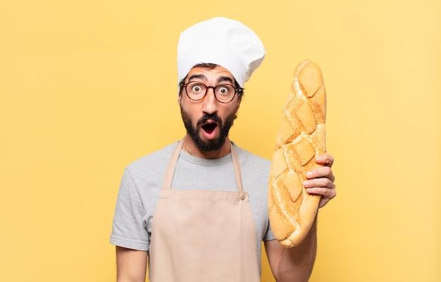 Jonge, bebaarde chef-kok, bange uitdrukking met een brood