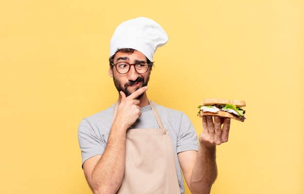 Jonge, bebaarde chef-kok die twijfelt of een onzekere uitdrukking heeft en een broodje vasthoudt