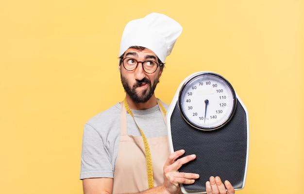 Jonge, bebaarde chef-kok die twijfelt of een onzekere uitdrukking heeft en een weegschaal vasthoudt