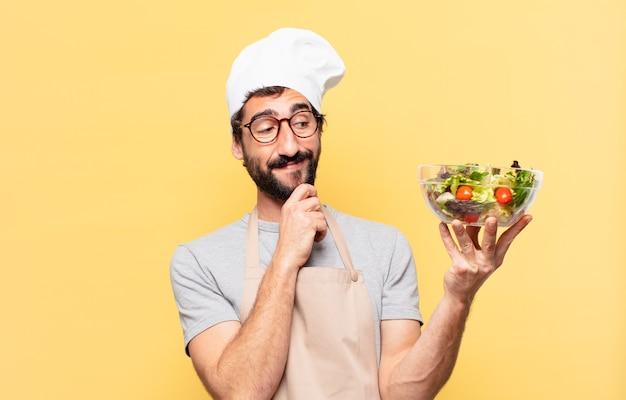 Jonge, bebaarde chef-kok die uitdrukking denkt en een salade vasthoudt