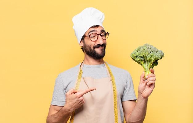 Jonge, bebaarde chef-kok die wijst of laat zien