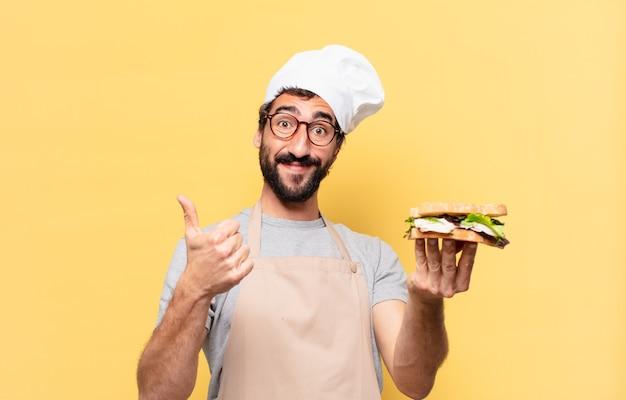 Jonge, bebaarde chef-kok man gelukkige uitdrukking en met een broodje