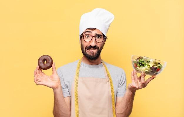 Jonge, bebaarde chef-kok met een twijfelende of onzekere uitdrukking die een salade en een donut vasthoudt