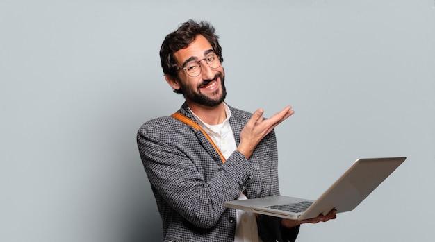 Jonge, bebaarde en gekke zakenman met een laptop