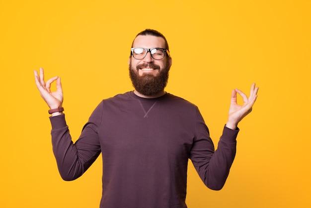 Jonge, bebaarde en vrolijke man zit in een ontspannen houding en draagt een bril in de buurt van gele muur