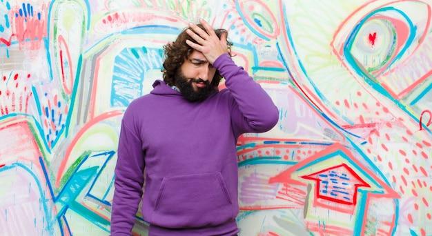 Jonge, bebaarde, gekke man die gestrest, moe en gefrustreerd kijkt, zweet van het voorhoofd droogt, zich hopeloos en uitgeput tegen een graffitimuur voelt