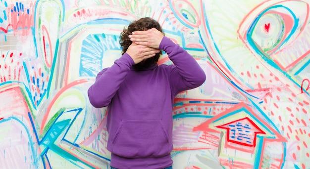 Jonge, bebaarde gekke man die gezicht bedekt met beide handen en nee zegt tegen de camera! afbeeldingen weigeren of foto's verbieden tegen een graffitimuur