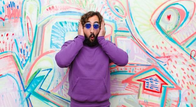 Jonge, bebaarde gekke man die onaangenaam geschokt, bang of bezorgd kijkt, mond wijd open en beide oren bedekt met handen tegen graffitimuur