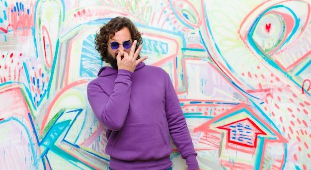 Jonge, bebaarde gekke man die walgt en zijn neus vasthoudt om te voorkomen dat hij een vuile en onaangename stank tegen de graffitimuur ruikt