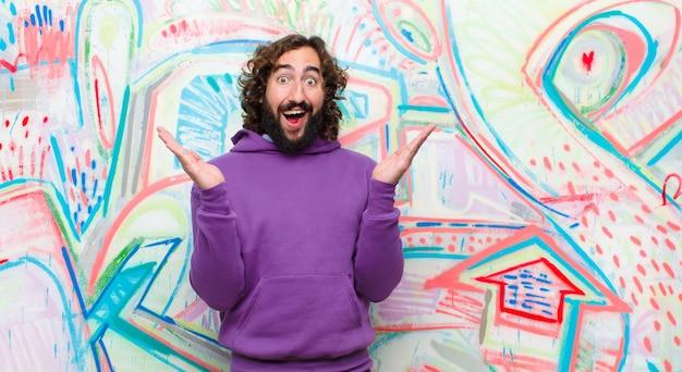 Jonge, bebaarde gekke man die zich blij, opgewonden, verrast of geschokt voelt, glimlachend en verbaasd over iets ongelooflijks tegen de graffitimuur