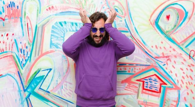 Jonge, bebaarde, gekke man die zich gestrest en angstig, depressief en gefrustreerd voelt met hoofdpijn, beide handen ophef tegen graffiti