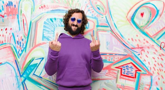 Jonge, bebaarde, gekke man die zich provocerend, agressief en obsceen voelt, de middelvinger wegknipt, met een opstandige houding op de graffitimuur