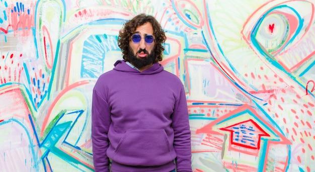 Jonge, bebaarde gekke man die zich verdrietig en zeurderig voelt met een ongelukkige blik, huilend met een negatieve en gefrustreerde houding tegen graffitimuur