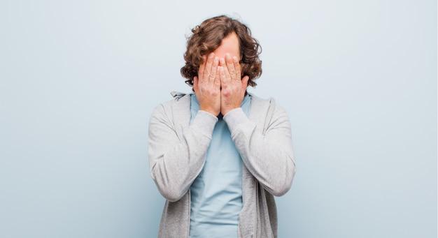 Jonge, bebaarde gekke man die zich verdrietig, gefrustreerd, nerveus en depressief voelt, het gezicht bedekt met beide handen, huilend tegen een egale kleur