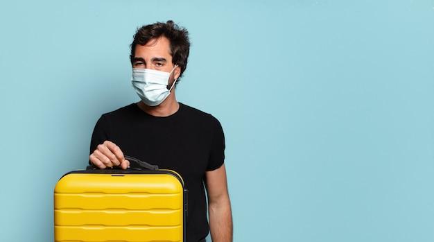 Jonge, bebaarde gekke man met een covid-beschermingsmasker. reisconcept