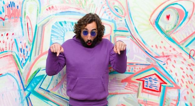Jonge, bebaarde gekke man met een schok, open mond en verbaasd, kijkend en naar beneden wijzend in ongeloof en verrassing tegen graffiti