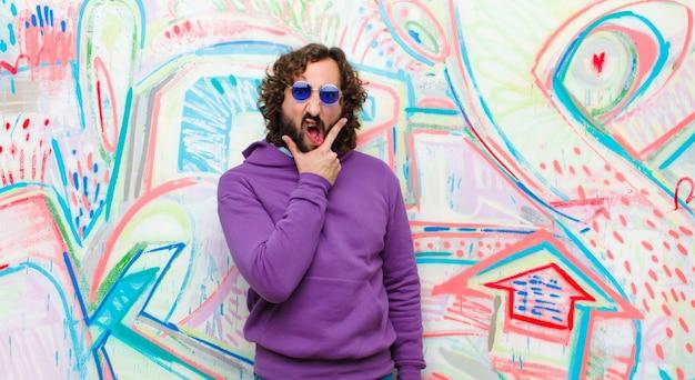 Jonge, bebaarde gekke man met mond en ogen wijd open en hand op kin, onaangenaam geschokt, zeggend wat of wow tegen graffitimuur