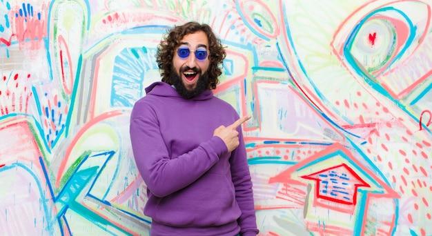 Jonge bebaarde gekke man op zoek opgewonden en verrast wijzend naar de zijkant en naar boven om ruimte op graffitimuur te kopiëren
