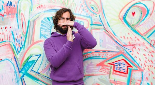 Jonge, bebaarde gekke man op zoek serieus, streng, boos en ontevreden, waardoor de tijd op graffiti muur tekent
