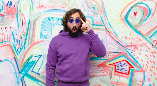 Jonge, bebaarde gekke man op zoek verrast, met open mond, geschokt, het realiseren van een nieuwe gedachte, idee of concept tegen graffiti muur