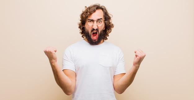 Jonge bebaarde gekke man schreeuwen agressief met een boze uitdrukking of met vuisten gebalde vieren succes tegen egale kleur