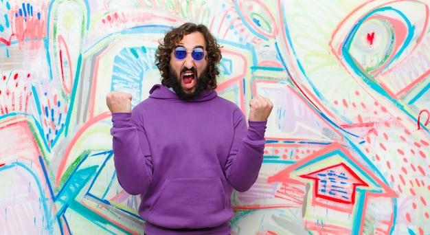 Jonge bebaarde gekke man schreeuwen agressief met een boze uitdrukking of met vuisten gebalde vieren succes tegen graffiti muur
