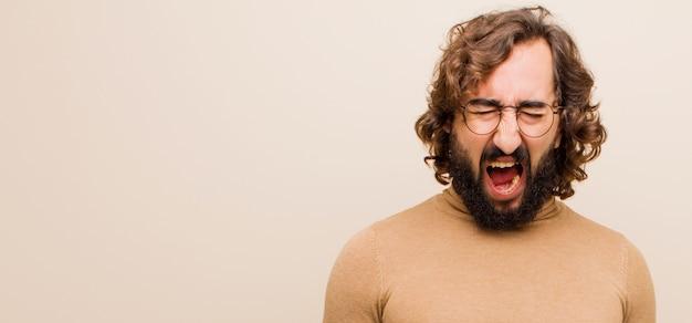 Jonge, bebaarde gekke man schreeuwt agressief, ziet er heel boos, gefrustreerd, verontwaardigd of geïrriteerd uit, schreeuwt nee tegen een effen muur