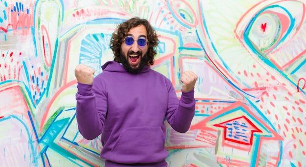 Jonge, bebaarde gekke man voelt zich blij, verrast en trots, schreeuwt en viert succes met een grote glimlach op graffitimuur