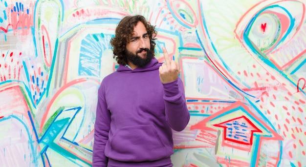 Jonge, bebaarde gekke man voelt zich boos, geïrriteerd, opstandig en agressief, draait de middelvinger weg en vecht terug tegen graffiti
