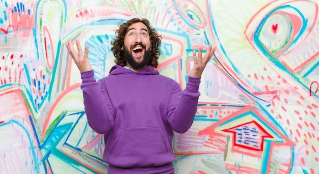 Jonge, bebaarde gekke man voelt zich gelukkig, verbaasd, gelukkig en verrast, viert overwinning met beide handen omhoog in de lucht tegen graffitimuur