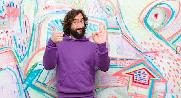 Jonge, bebaarde gekke man voelt zich gelukkig, verbaasd, tevreden en verrast, toont oké en duimen omhoog gebaren, glimlachend op graffiti muur