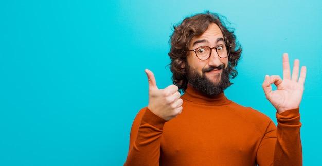 Jonge, bebaarde gekke man voelt zich gelukkig, verbaasd, tevreden en verrast, toont oké en duimen omhoog gebaren, glimlachend tegen vlakke kleur muur
