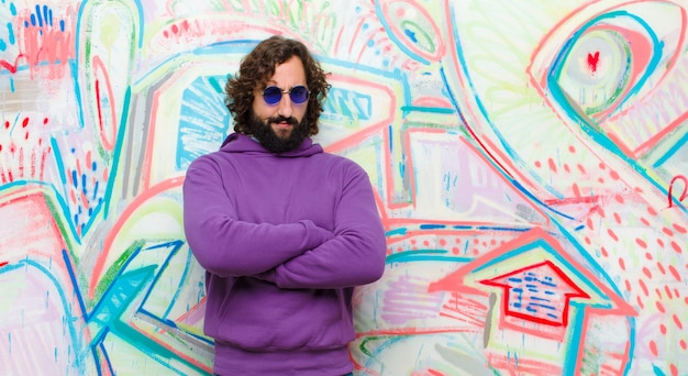 Jonge, bebaarde gekke man voelt zich ontevreden en teleurgesteld, kijkt ernstig, geïrriteerd en boos met gekruiste armen op graffitimuur