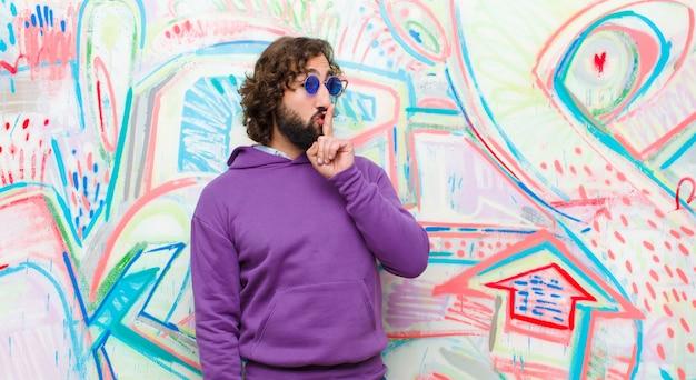 Jonge, bebaarde gekke man vraagt om stilte en stilte, gebaart met vinger voor mond, zegt shh of houdt een geheim tegen graffiti