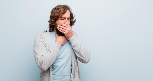 Jonge, bebaarde gekke man ziek voelen met een zere keel en griep symptomen, hoesten met mond bedekt