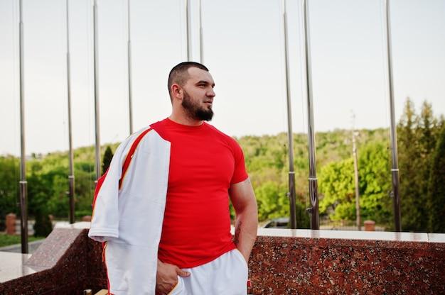 Jonge, bebaarde gespierde man slijtage op wit sport pak met rood shirt
